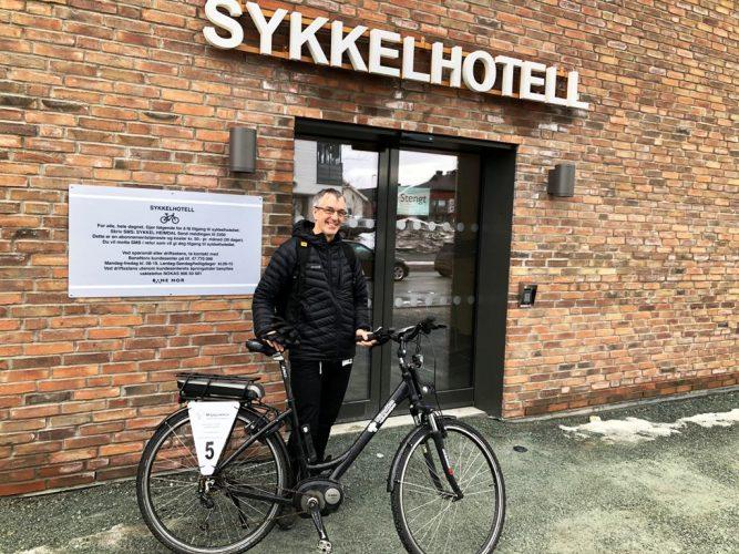 """Miljøpakkens sykkelguru Richard Sanders foran byens følrste sykkelhotell. """"Stengt""""-skiltet på døra forsvant like etter."""